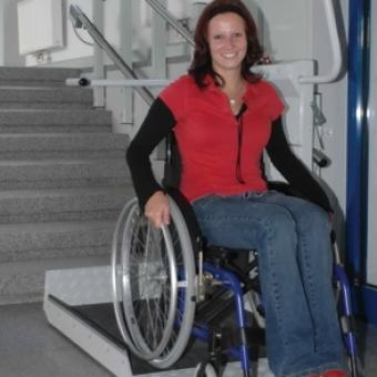 Smiling woman in a wheelchair using the Savaria Delta Inclined Platform Lift
