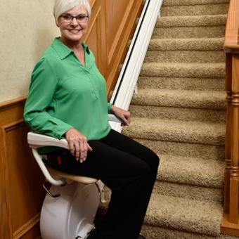 Woman sitting on the Savaria K2 Straight Stair Lift