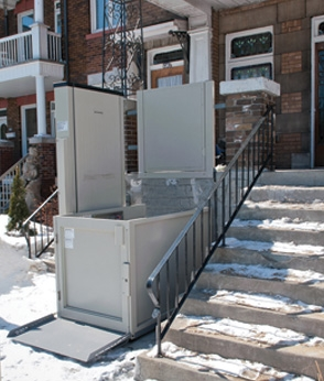 Savaria Multilift Vertical Platform Lift in front of a home next to snow-covered steps